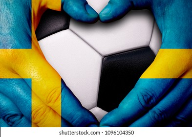 Hands painted with a Sweden flag forming a heart over soccer ball background