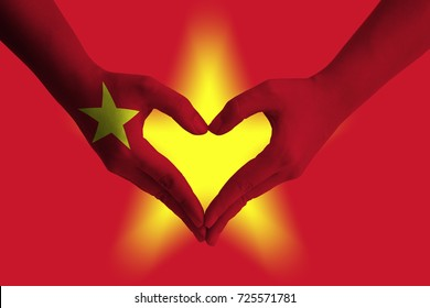 Hands painted as the VIETNAM flag forming a heart