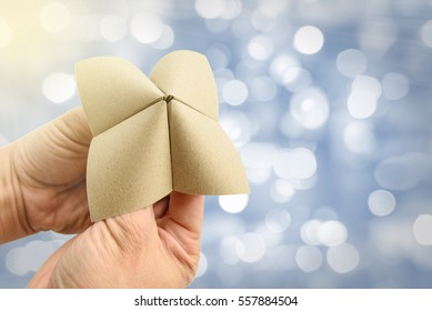 Hands in a paper fortune teller make multiple decisions. The person operating the fortune teller manipulates the device based on choices made by player, and finally one of hidden messages is revealed.