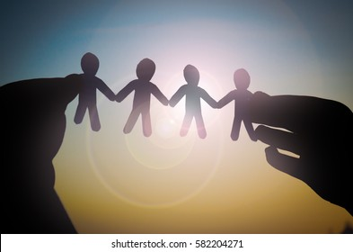 hands with paper humans contour on the sun background business concept and team