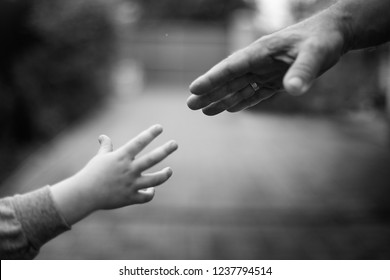Hands of parent and child on background