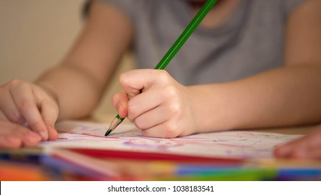 Hands of parents and child drawing together, happy family having fun together