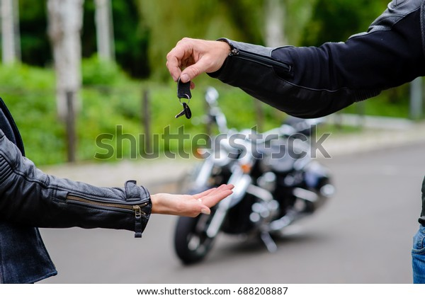 Hands pass the keys to the motorbike.