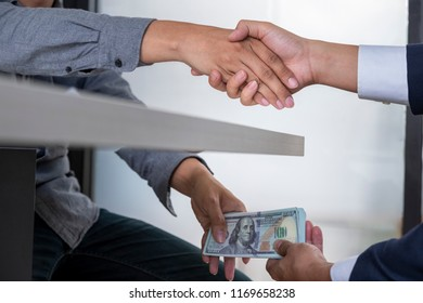 Hands passing money under table corruption bribery, businessman sealing the deal with a handshake and receiving a bribe money.