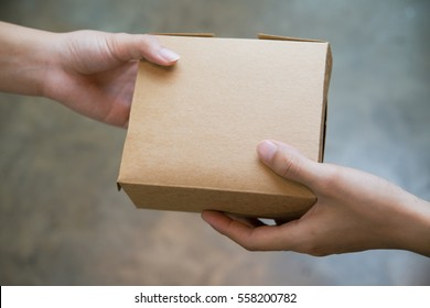 hands passing and receiving small brown paper box.