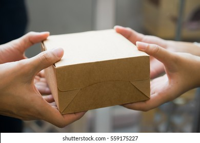 hands passing and receiving small brown box package.
