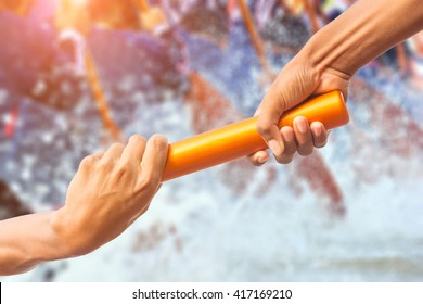 hands passing a relay baton on rowing team background and color tone effect.