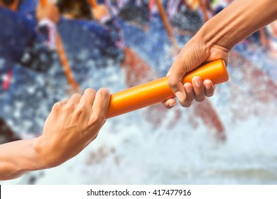 hands passing a relay baton on rowing team background