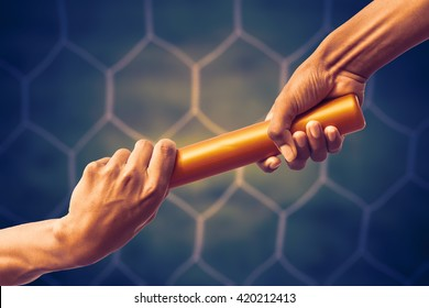 hands passing a relay baton on on soccer goal net background with vintage color tone effect.