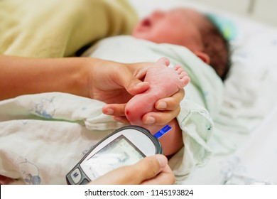 Hands of pediatric nurse hold and using blood and glucose meter with sheet check and sick newborn baby foots to checkup glucose in his blood at NICU wards.