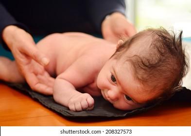 Hands of Pediatrician nurse checks infant baby body development examination.