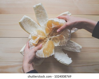Hands peeled pomelo on a wooden table. The view from the top. Toning.