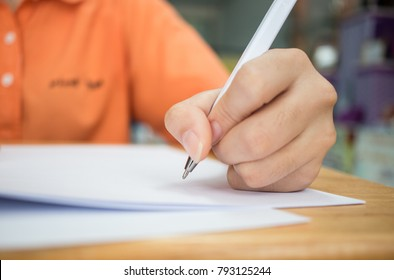 Hands with pencil over application form, Students taking exams, writing examination room with undergraduate students inside. Student sitting learning lessons doing final exam in classroom.