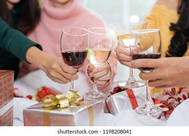 Hands of people celebrating New year party in home with wine drinking glasses and present background. New year eve and Christmas party concept. Happiness and Friendship and Funny together. Clink glass