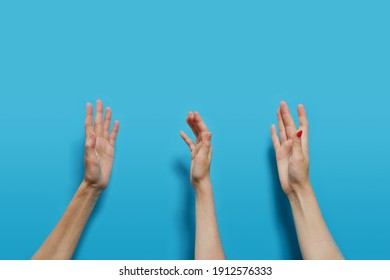 The hands of people faceless of Caucasians are raised up on a blue background.