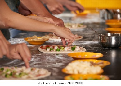 Hands of people making pizzas together