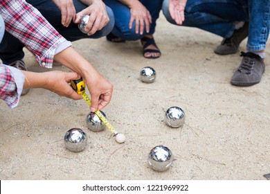 Hands of people playing petanque on sand together on weekend