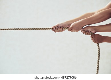 Hands of people pulling tug of war