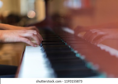 Hands of a person playing a brown grand piano