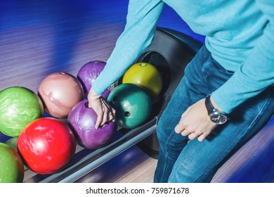 The hands of a person who chooses a bowling bowl. A man plays bowling. Choose the color of the ball.