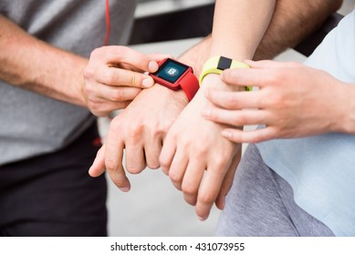 Hands of persons with smart watches