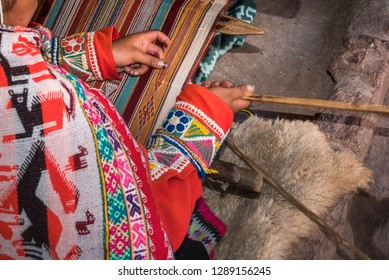 Hands of Peruvian weaver making a blanket on a wooden frame