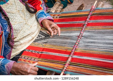 Hands of Peruvian weaver making a striped textile on a wooden frame