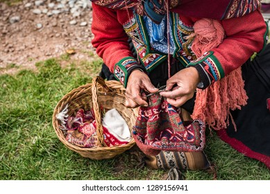 Hands of a Peruvian women knitting with basket setting on the ground