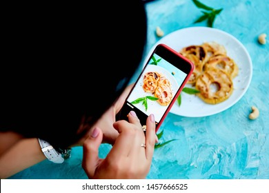 Hands with the phone close up pictures of food. Blogger girl. Food photo. Food blogger using smartphone taking photo. Grilled apples with cinamon on white plate on blue background.