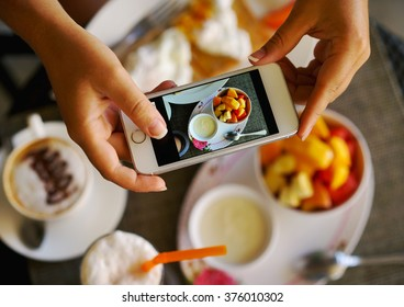 Hands with the phone close-up pictures of food. Breakfast for two : yogurt, coffee, fruit , toast.