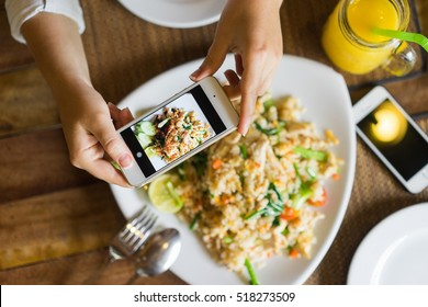 Hands with the phone close-up pictures of food. Fried rice with chicken and mango shake, one dish for two.