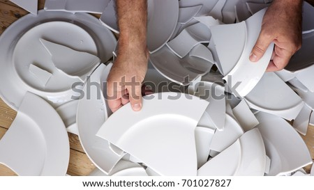 hands picking up broken white plates from wooden floor