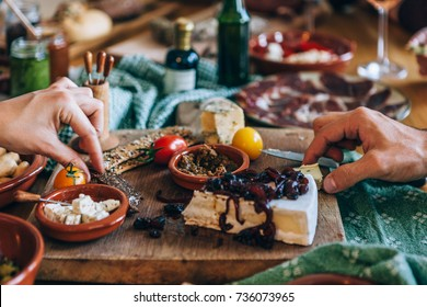 hands picking food on a party table