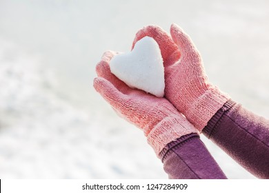 Hands in pink gloves holding snow heart. Winter time