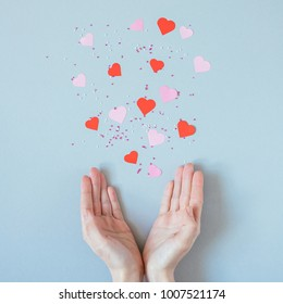 Hands with pink and red paper hearts on the blue background, top view. Valentines day background.