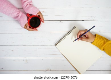 Hands in pink sweater holding red coffee cup with hand in mustard yellow sweater holding polka dot pencil to write some text or messages on blank white writing paper space e.g. New Year's Resolutions