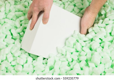 Hands placing a white cardboard box in polystyrene loosefill for protection