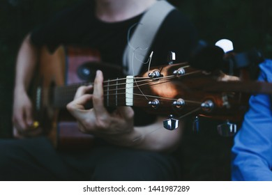 Man's hands playing acoustic guitar, close up. Travel, tourism leisure time concept.