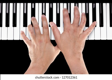 Hands playing a chord of Ab major over C bass on a piano keyboard shot from above with a black background.