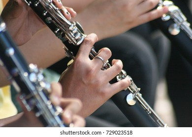 Hands playing clarinets at a marching band performance