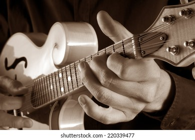 hands playing a classic bluegrass mandolin,sepia image