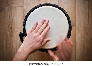 hands playing djembe drum