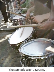 Hands playing drums with drumsticks