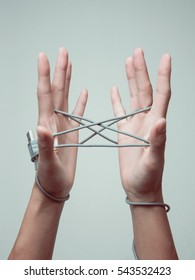 """Hands are playing game """"cat's cradle"""" with usb cable"""