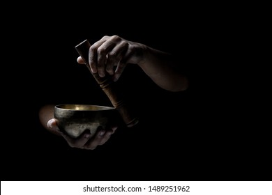 Hands  playing an old tibetan singing bowl. Black background. Music therapy