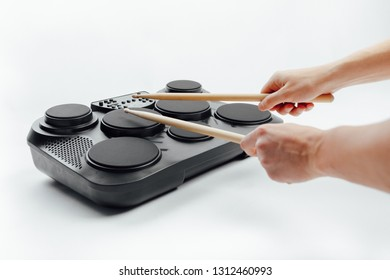 hands playing on portable electronic drums, white background