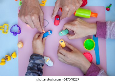 hands playing with plasticine toys