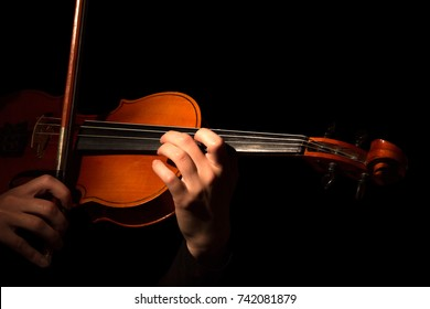 Hands playing the violin isolated on black background