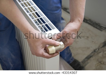 hands of a plumber installing a connection at a radiator