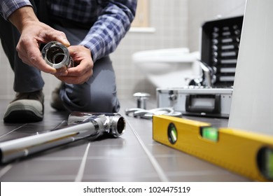 hands plumber at work in a bathroom, plumbing repair service, assemble and install concept